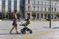 Mother pushing baby in a stroller in the city - MOMF00613