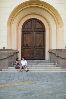Couple in love sitting on a stairs in the city - MOMF00622