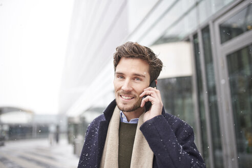 Smiling young businessman on cell phone in snow - PNEF01224