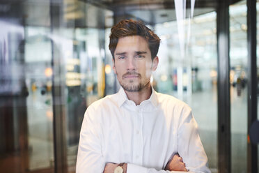 Portrait of confident young businessman behind glass pane - PNEF01227