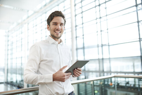 Portrait of happy young businessman with tablet - PNEF01233