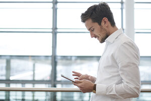Smiling young businessman using tablet - PNEF01236