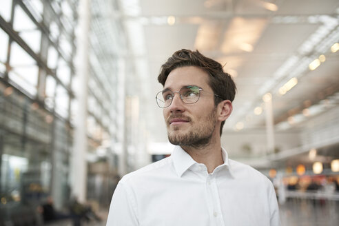 Portrait of young businessman wearing glasses looking around - PNEF01245