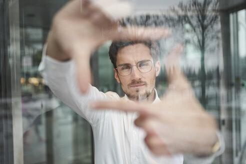 junger business mann mit brille hinter fensterscheibe formt mit finger einen rahmen,  münchen, bayern, deutschland - PNEF01248