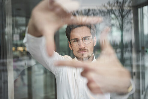 Portrait of young businessman behind glass pane shaping a finger frame - PNEF01248