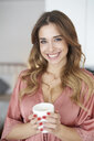 Portrait of smiling young woman in dressing gown holding cup of coffee - PNEF01254