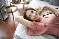 Smiling young woman in dressing gown lying in bed - PNEF01263