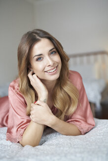 Portrait of smiling young woman in dressing gown lying in bed - PNEF01266