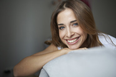 Portrait of happy young woman on couch - PNEF01284