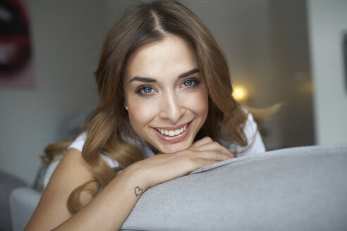 Portrait of smiling young woman on couch - PNEF01287