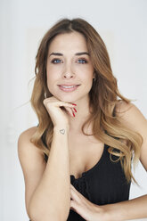 Portrait of smiling young woman wearing black dress - PNEF01290