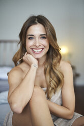 Portrait of happy young woman sitting on bed - PNEF01305