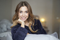 Portrait of smiling young woman on couch - PNEF01308