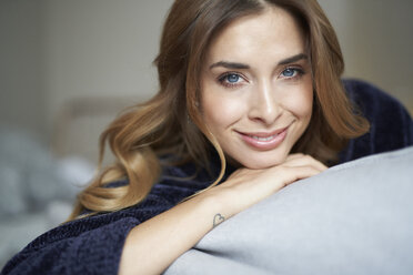 Portrait of smiling young woman on couch - PNEF01311