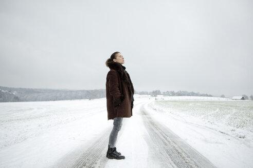 Mature woman standing on field way in winter - FLLF00059