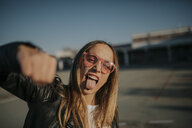 Portrait of young woman outdoors sticking out tongue and punching - DMGF00004