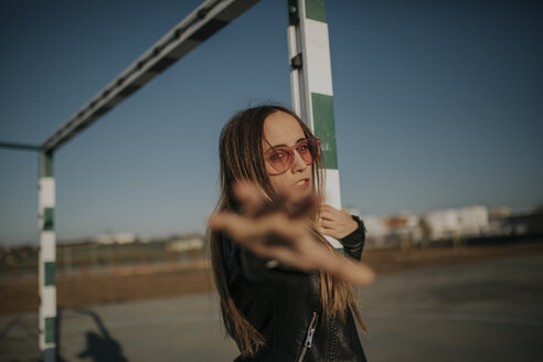 Portrait of young woman wearing sunglasses on sports field reaching out her hand - DMGF00007