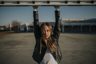 Portrait of young woman hanging at goal on sports field - DMGF00010