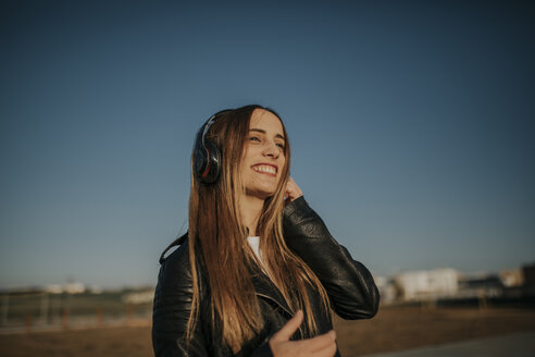 Happy young woman listening music with headphones outdoors - DMGF00013
