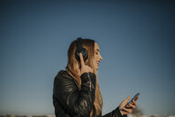 Happy young woman listening music with headphones outdoors - DMGF00019