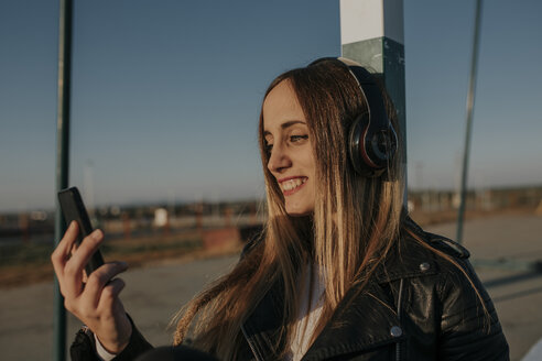 Smiling young woman with headphones and cell phone leaning against goal on a sports field - DMGF00025