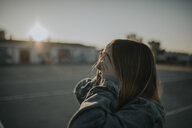 Young woman covering her eyes at sunset - DMGF00034
