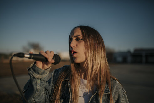 Pozoblanco, Cordoba, Spain, Urban girl singing with a microphone in the hand, youth culture - DMGF00037