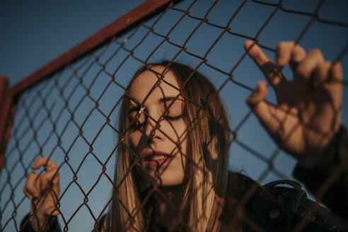 Pozoblanco, Cordoba, Spain, Urban girl looking through a fence, youth culture - DMGF00043