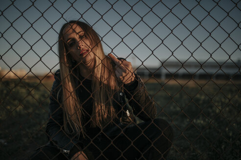 Portrait of young woman sitting behind wire mesh fence giving the finger - DMGF00046