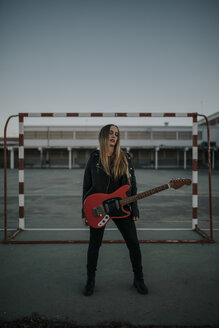 Portrait of cool young woman with guitar on sports field - DMGF00049