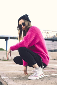 Portrait of fashionable young woman wearing sunglasses, cap and pink knit pullover - ACPF00430
