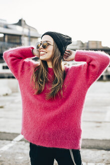 Portrait of fashionable young woman wearing sunglasses, cap and pink knit pullover - ACPF00433