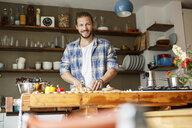 Young man preparing food at home, slicing bread - PESF01109