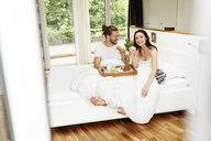 Affectionate couple having breakfast in bed - PESF01115