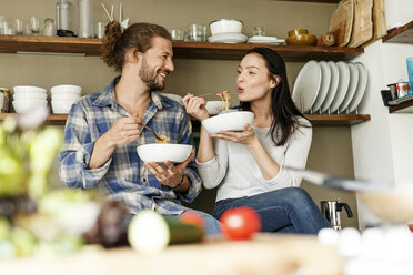 Happy couple sitting in kitchen, eating spaghetti - PESF01127