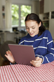 Young woman sitting at home, using digital tablet - PESF01130