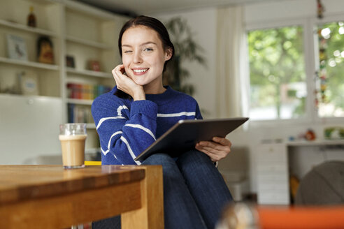 Young woman sitting at home, using digital tablet - PESF01139