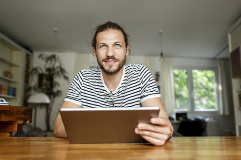 Young man with a bun sitting at home, using digital tablet - PESF01148