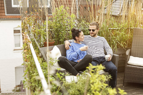 Young couple relaxing on their balcony, sitting on couch - PESF01157
