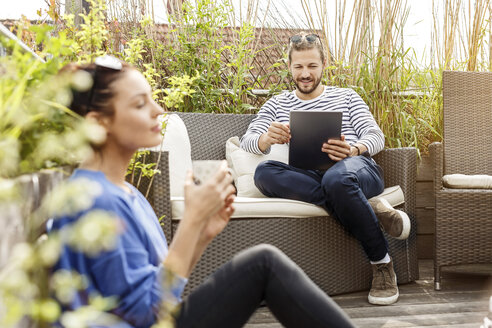 Young couple relaxing on their balcony, man sitting on couch, using laptop - PESF01163