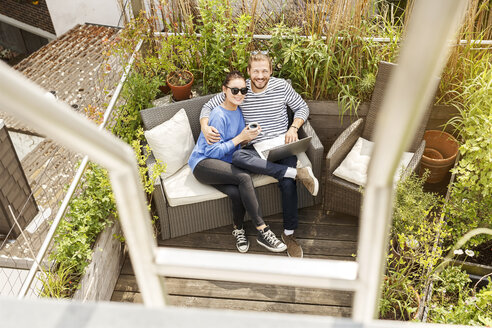 Young couple relaxing on their balcony, sitting on couch, using laptop - PESF01166