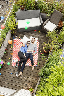 Young couple relaxing on their balcony, lying on blanket with arms around - PESF01172
