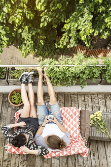 Young couple relaxing on their balcony in summer, drinking coffee - PESF01178