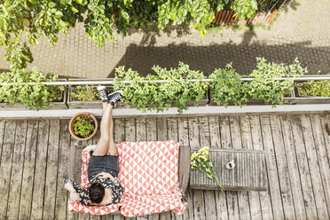 Young woman relaxing on her balcony in summer - PESF01181