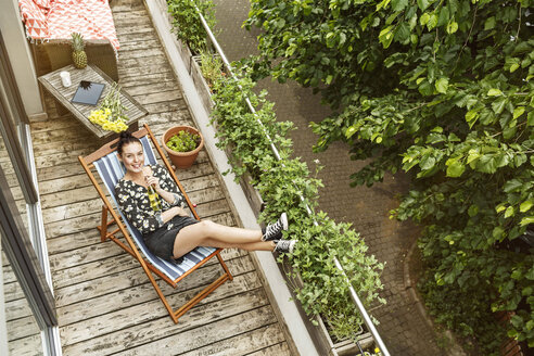 Young woman sitting in deck chair, relaxing on her balcony - PESF01187