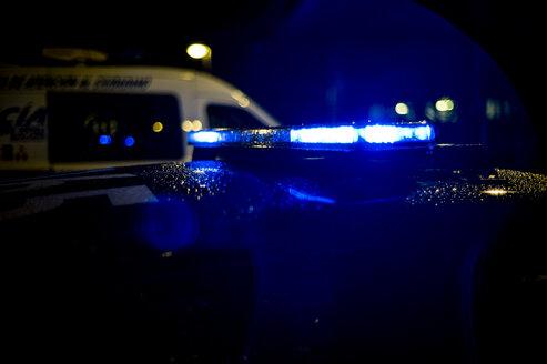 Rain falls on a police car at night in Madrid Spain. - OCMF00255