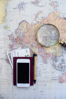 Travel planning with a world map, money, cell phone and magnifying glass - IGG00750