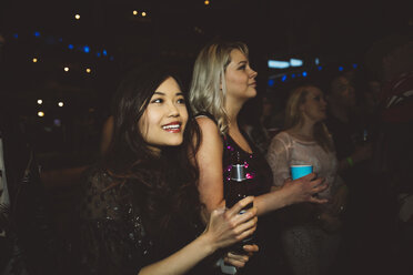 Smiling young female millennial friends drinking and partying in nightclub - HEROF17020