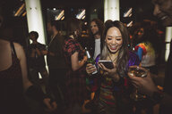 Smiling young female millennial drinking beer and texting with smart phone at nightclub - HEROF17029