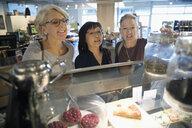 Senior women friends browsing desserts at display case in bakery - HEROF17065